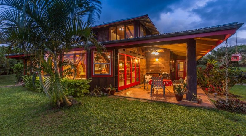 Back exterior of a beautiful Big Island property with red trim, red door, and accents. Photo Courtesy of Algood Hawaii LLC